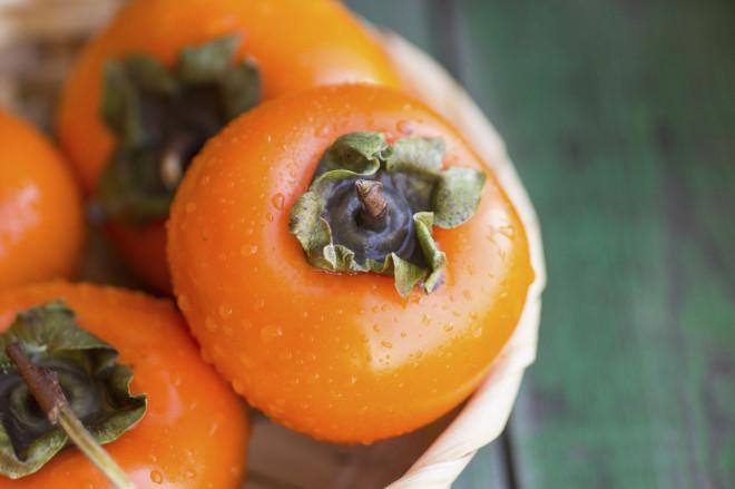 ripe persimmons in a wicker basket