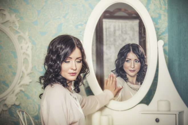 鏡から目を逸らす女性