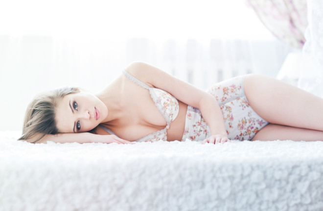 sexy young woman in lingerie lying on bed