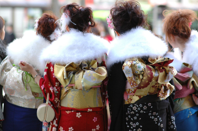 The backs of four women waiting in anticipation of an event