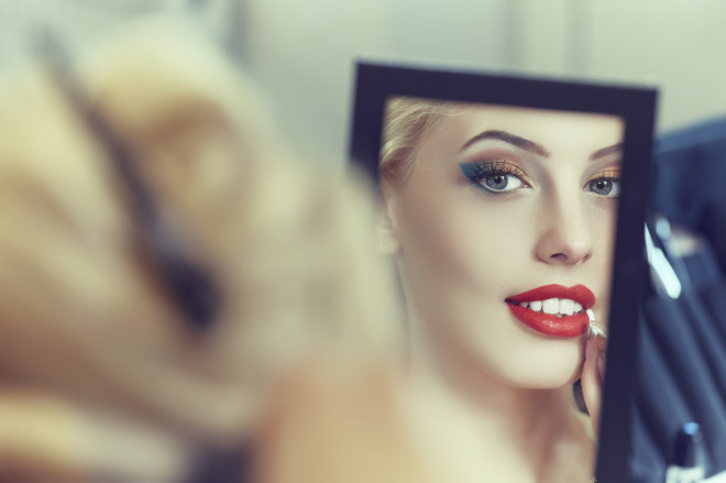 Beautiful young woman applying red lipstick in mirror