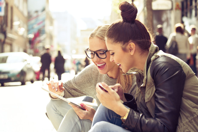 Two young women with tablet on street