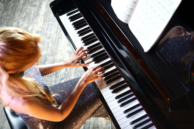Woman playing piano in concert.