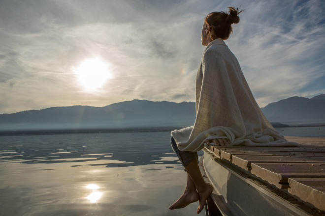 Young woman relaxes on lake pier with blanket, watches sunset