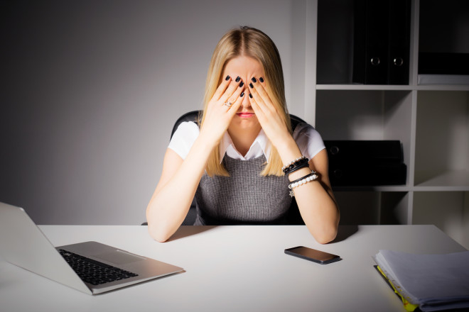 Woman sitting in her office with her eyes covered