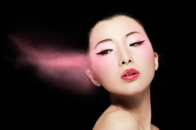 Asian model with pink powder isolated on black.