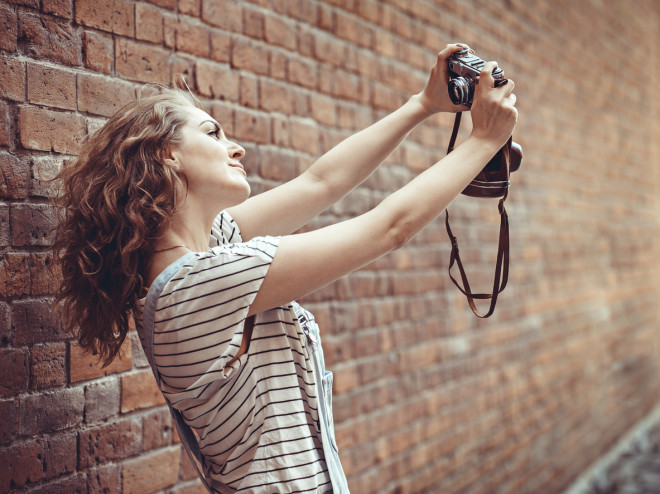 Beautiful girl making selfie with camera  in park