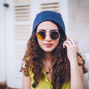 Hip hop style female with sunglasses and winter cap