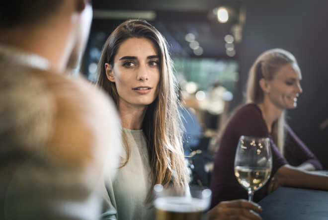 Beautiful young female looking at friend in bar