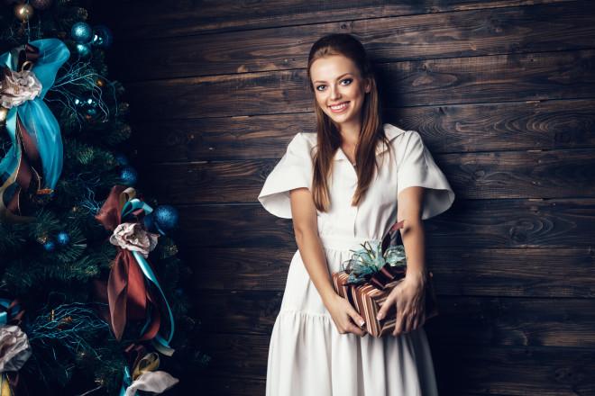 Cute girl in white dress holding gift box
