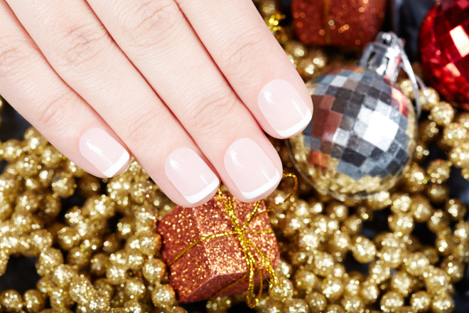 Hand with french manicured nails and Christmas decorations