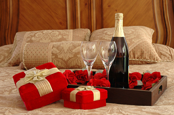 Romantic setting of wine and presents on a bed