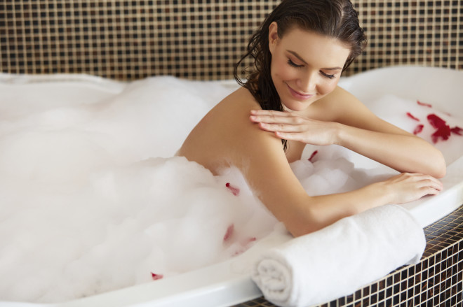 Spa Woman. Beautiful Woman in Bath Cares About Her Hands.