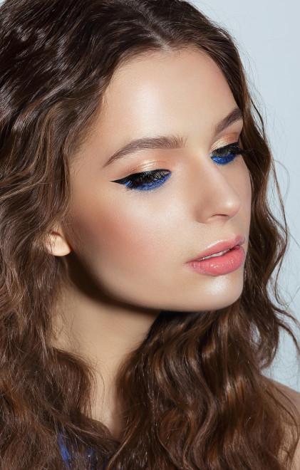 Visage. Pensive Woman with Blue Mascara and Holiday Makeup