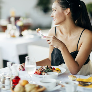 Beautiful woman eating meal in restaurant