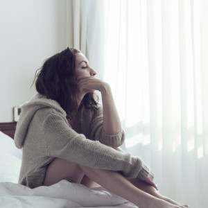 Pensive woman in bed