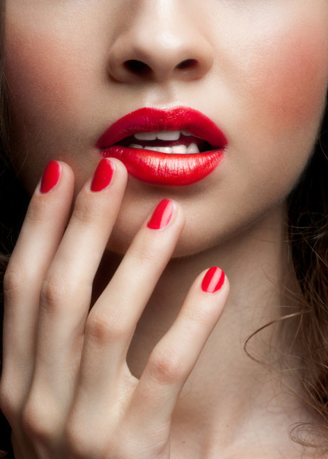 Close-up of a woman's red lip and nails