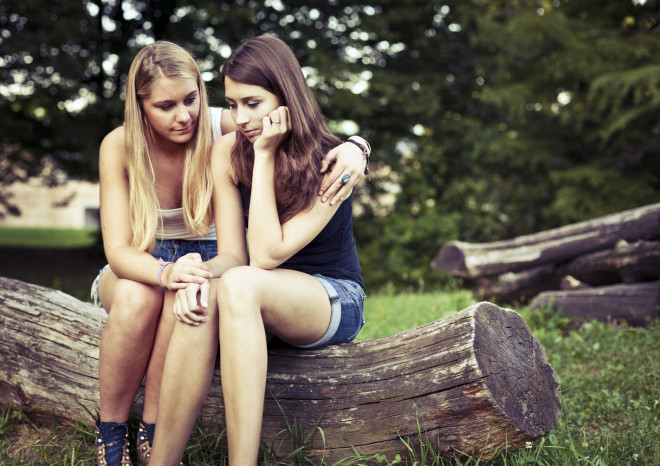 A teenager consoling her friend who looks sad