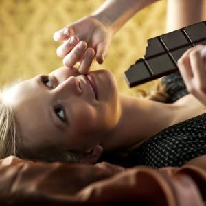 Beautiful young woman eating chocolates.