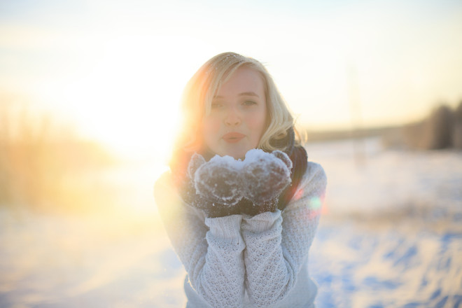 Beautiful blonde girl standing in winter snow-covered road