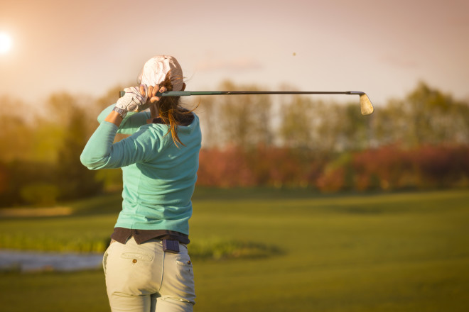 Woman golf player hitting ball.