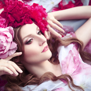 woman in a wreath of peonies lies among petals