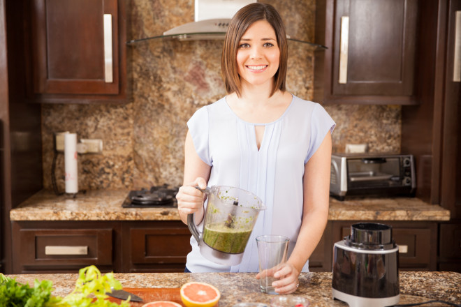 Cute girl making green juice