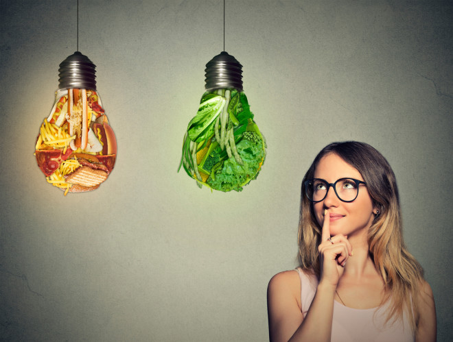 woman looking at junk food green vegetables shaped lightbulb