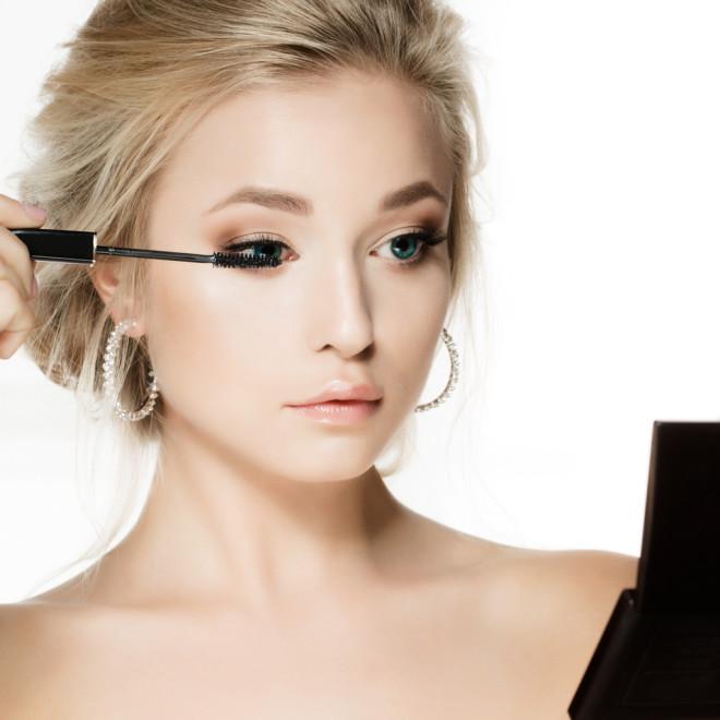 Woman applying make-up, mascara