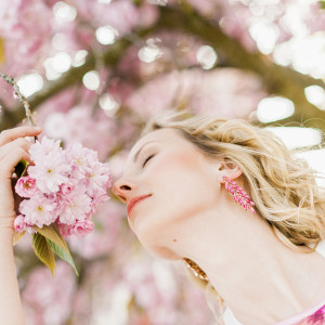 Woman outdoors in park by pink blossom tree