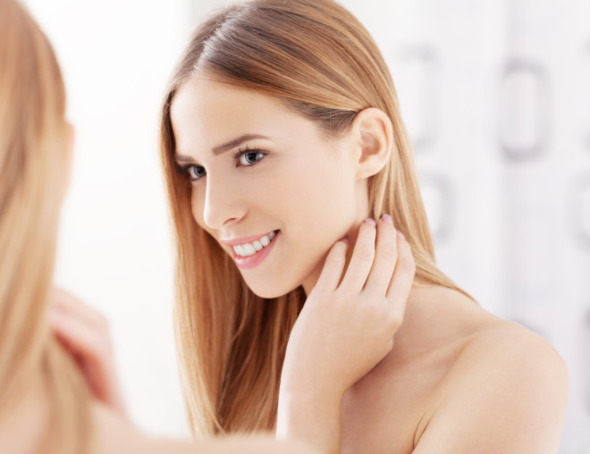 Young woman looking in the mirror and smiling