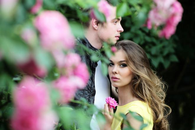 Young couple embraces near rose bush