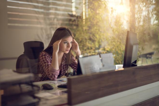 Worried businesswoman using desktop PC in the office.