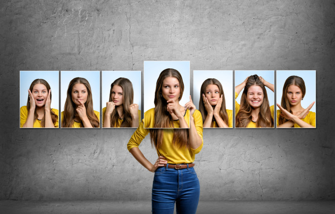 Girl holds and changes her face portraits with different emotions
