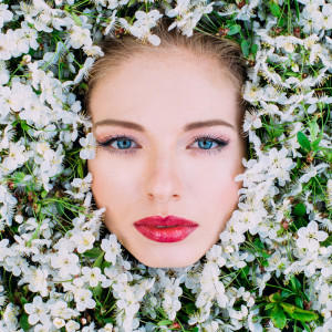 Portrait of beautiful young woman  among the cherry flowers