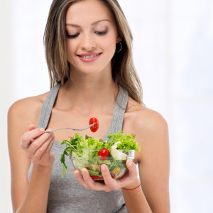 Young girl eating fresh salad