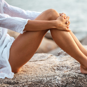 Luxury young woman legs with plumeria flower