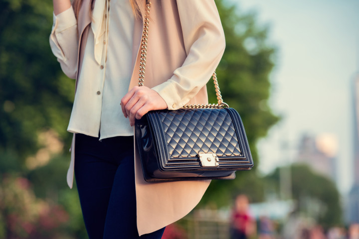 Woman carrying elegant purses bag at city park