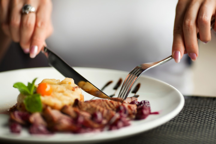 Woman using knife and fork to cut her dinner