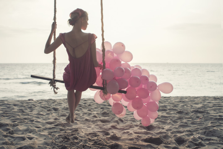beautiful women at swing with pink ballons