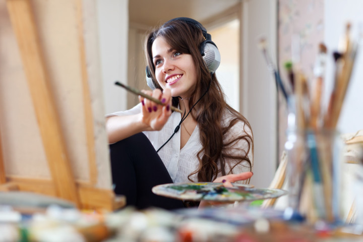 Long-haired  artist  in headphones paints picture