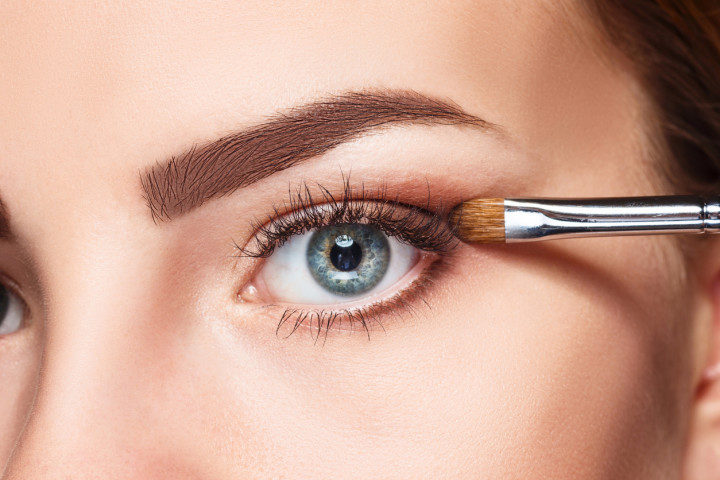 Beautiful female eyes with make-up and brush