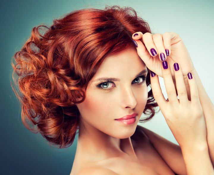 Pretty redhaired girl with curls and fashionable makeup.