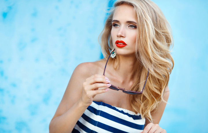 Summer portrait of beautiful woman on blue background