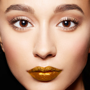 Closeup of woman face.perfect skin, gold lips,long eyelashes.