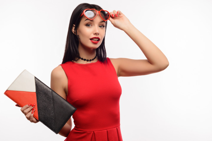 fashionable surprised young lady in a red dress and clutch holds on to sunglasses in the shape of a heart