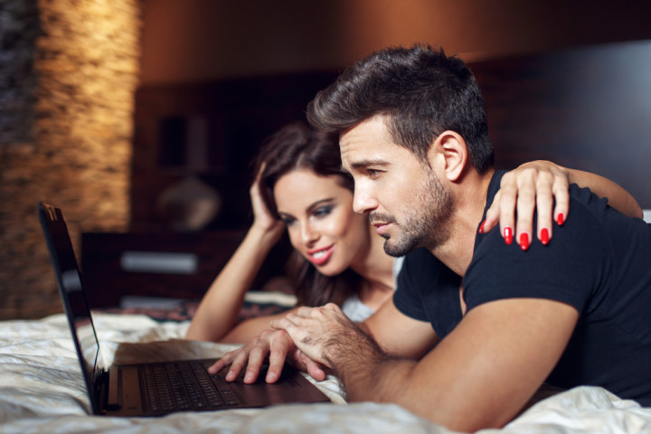 Couple prone on bed with laptop