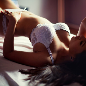 Beautiful girl lying on the bed in white sexy lingerie