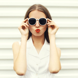 Fashion portrait of pretty young woman in white sunglasses