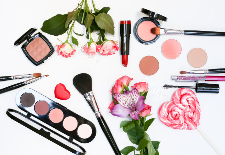 Composition with makeup cosmetics, brushes, shadoes and flowers on white